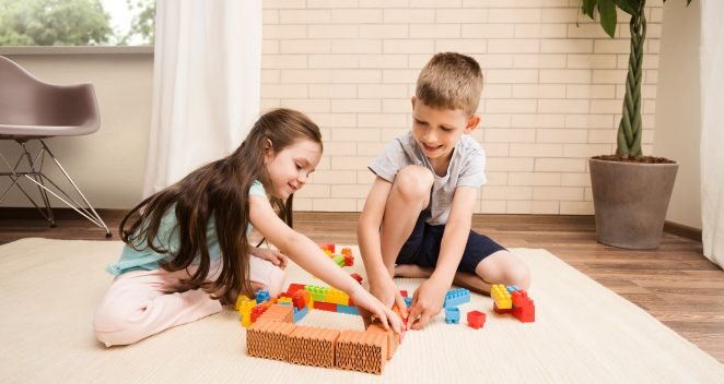Children playing with miniature bricks and plastic building blocks