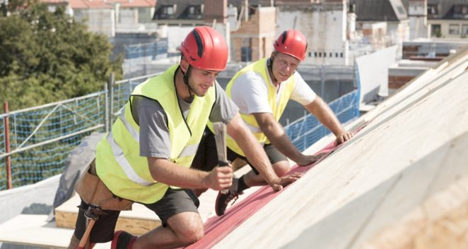 Urban roofers applying roof underlay sheet wearing hard hat and safety jacket in team work