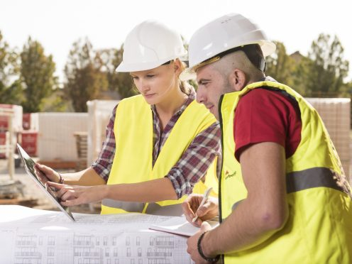 Woman pointing at tablet with male coworker taking notes at construction site, Fast Forward Commercial Excellence
