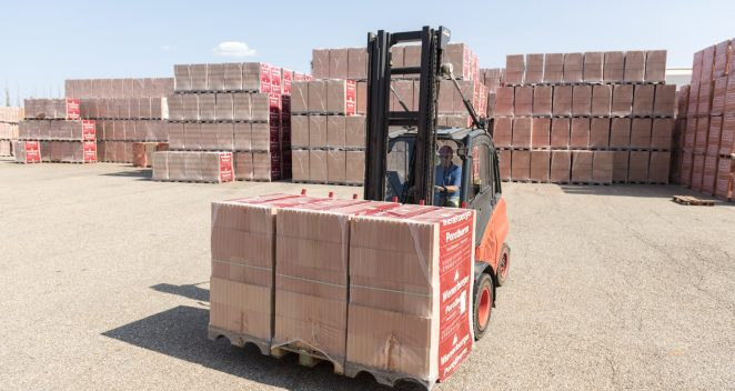 Forklift loads clay block pallets on tuck on stockyard