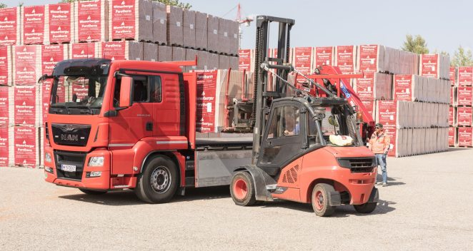 Forklift loads clay block pallets onto truck at stockyard